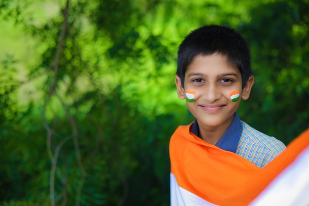Giovane bambino indiano con bandiera indiana sul viso