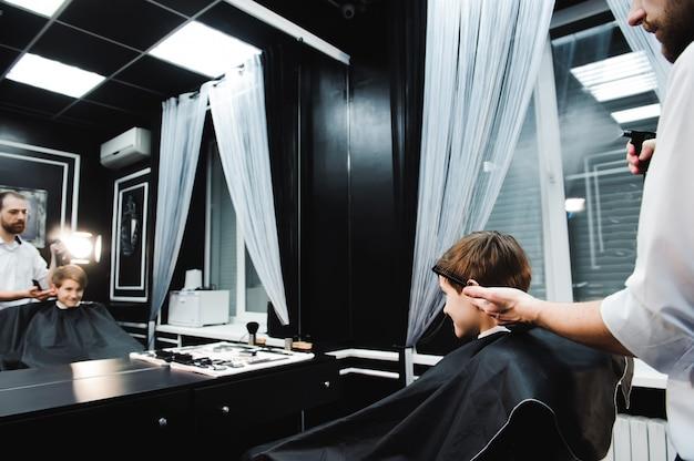Giovane barbiere bello che fa taglio di capelli del ragazzo sveglio in parrucchiere.