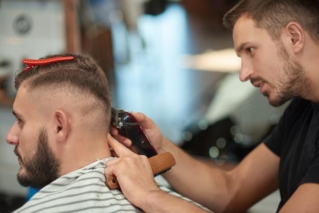 Giovane barbiere maschio professionista che si concentra mentre dà al suo cliente un taglio di capelli.