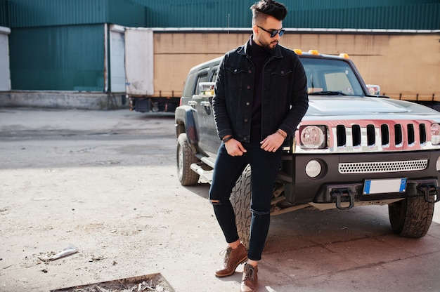 Giovane barbuto alla moda che posa all'aperto con la grande automobile