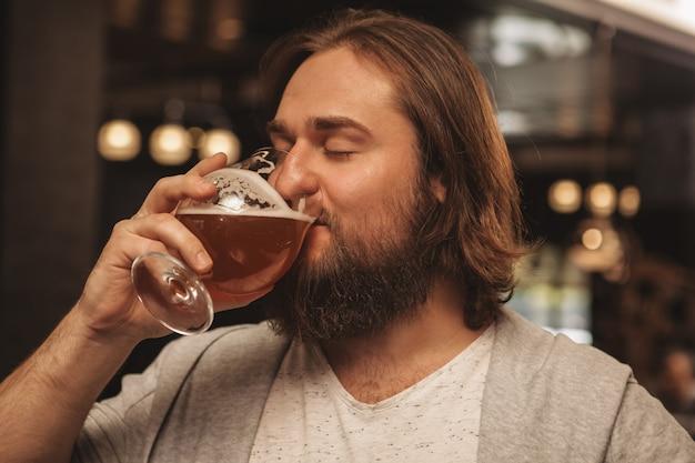 Giovane barbuto che gode bevendo birra al pub