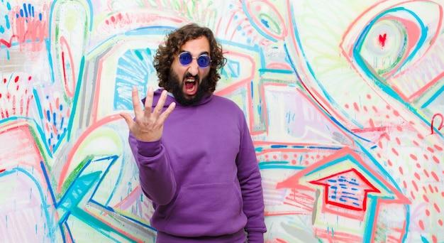 Giovane barbuto pazzo che sembra arrabbiato, infastidito e frustrato urlando wtf o cosa c'è che non va in te contro il muro dei graffiti
