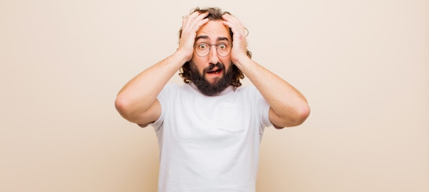 Giovane barbuto pazzo che si sente inorridito e scioccato, alzando le mani alla testa e in preda al panico per un errore contro il colore piatto