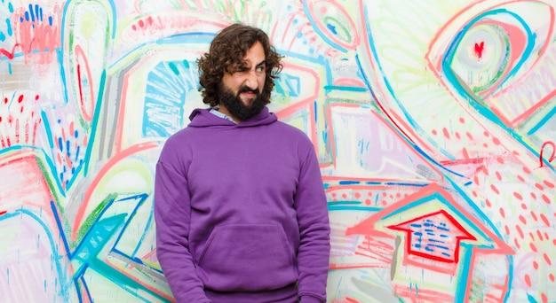 Giovane barbuto pazzo che si sente triste, arrabbiato o arrabbiato e guarda di lato con un atteggiamento negativo, accigliato in disaccordo sul muro di graffiti