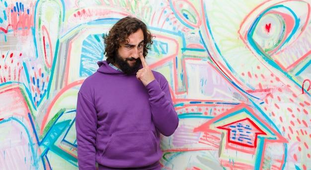 Giovane barbuto pazzo che ti tiene d'occhio, non fidandosi, guardando e rimanendo vigile e vigile contro i graffiti