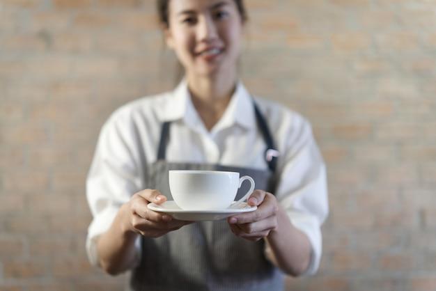 Giovane barista asiatico sveglio in camicia piacevole con il grembiule che serve caffè caldo nella tazza bianca in caffetteria.