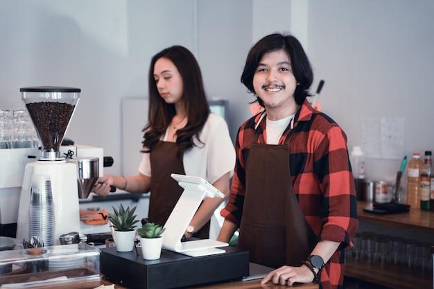 Giovane barista che sorride alla macchina fotografica