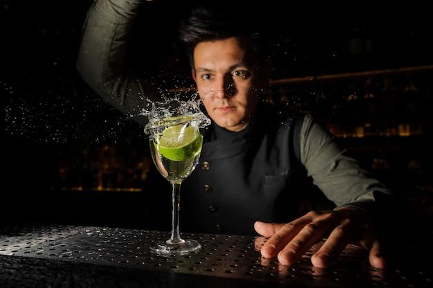 Giovane barista e un bicchiere da cocktail con spruzzi di bevanda alcolica e calce in esso