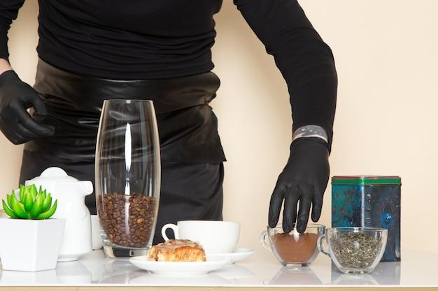 Giovane barista in abito da lavoro nero con ingredienti e attrezzatura per il caffè semi di caffè marrone indossando maschera sterile nera su bianco