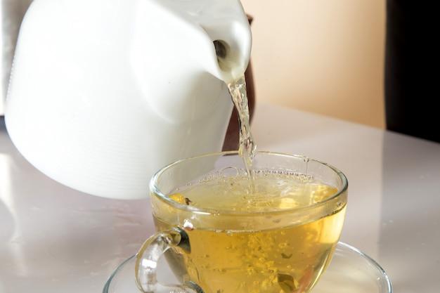 Giovane barista in abito da lavoro nero con ingredienti e attrezzatura per il caffè semi di caffè marrone makign un tè su bianco