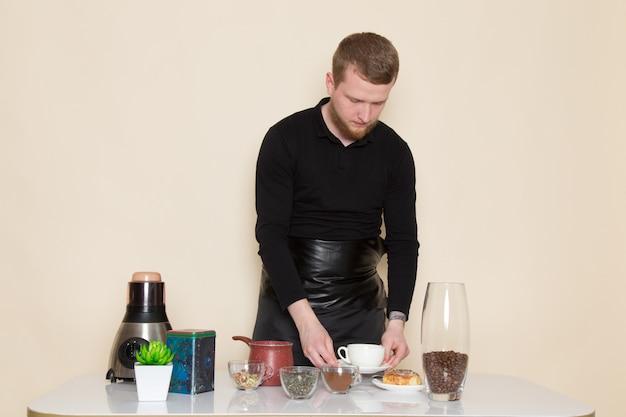 Giovane barista in abito da lavoro nero con ingredienti e attrezzature da caffè semi di caffè marrone su bianco
