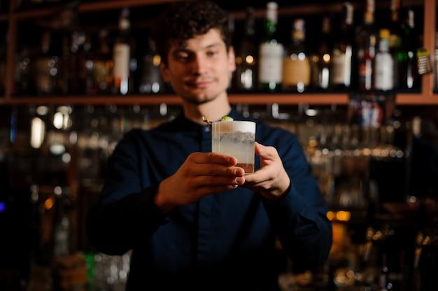 Giovane barista riccio che tiene un bicchiere con cocktail estivo agrodolce