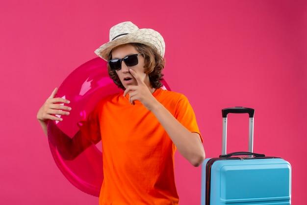 Giovane bel ragazzo in maglietta arancione e cappello estivo indossando occhiali da sole neri guardando la fotocamera con espressioni pensive pensando di avere dei dubbi in piedi con la valigia di viaggio su sfondo rosa