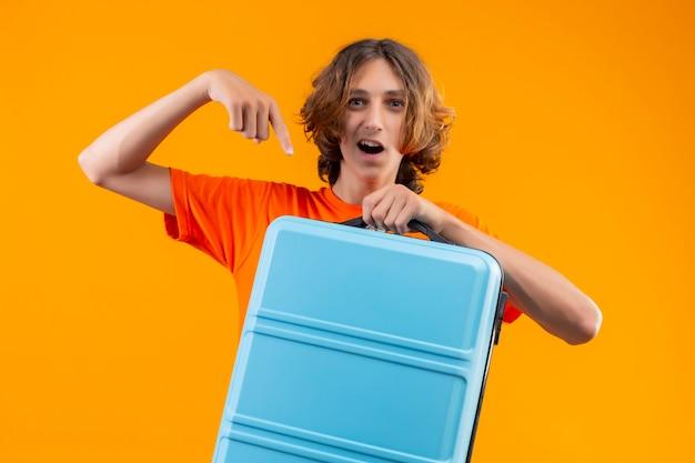 Giovane bel ragazzo in maglietta arancione in piedi con la valigia da viaggio che punta con il dito ad esso guardando fiducioso e felice su sfondo giallo
