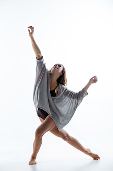 Giovane bella ballerina in abito beige danza sul muro bianco