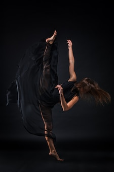 Giovane bella ballerina in abito beige danza sul nero