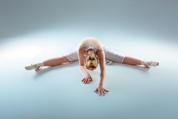 Giovane bella ballerina warm-up