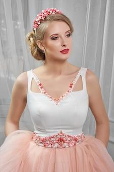 Giovane bella, bella donna in abito corto rosa chiaro con il rosso