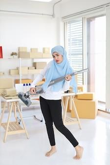 Giovane bella bella donna musulmana asiatica felice che pulisce e che gioca la pulizia di vuoto come la chitarra con il fondo della scatola del pacchetto di commercio elettronico e della pmi. ragazza delle pulizie in leggings neri che aspirano la sua stanza.