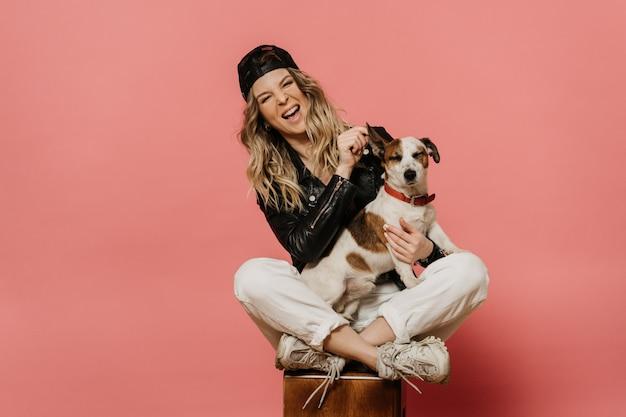 Giovane bella bionda in giacca di pelle nera, jeans bianchi e un cappello seduto con il suo cucciolo. ridendo. in attesa della fine della pandemia di coronavirus, isolata sul rosa con spazio di copia. concetto di covid-19.