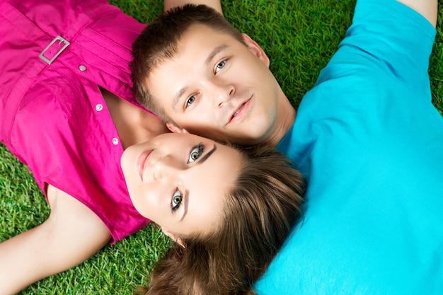 Giovane bella coppia che stabilisce insieme sull'erba nel parco. vista dall'alto. concetto di amore e solidarietà.