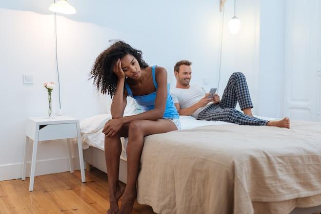 Giovane bella coppia interrazziale a letto stressata con problemi di infedeltà