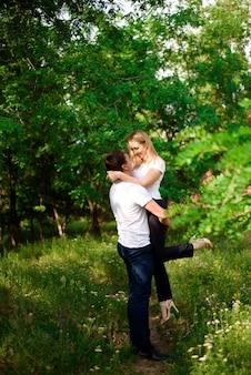 Giovane bella coppia mano nella mano sul paesaggio naturale.