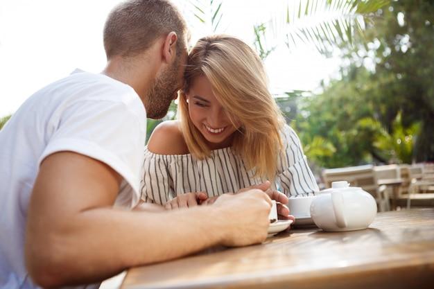 Giovane bella coppia parlando, sorridendo, riposando nella caffetteria.
