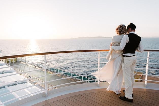 Giovane bella coppia sul ponte di una nave da crociera nel mare