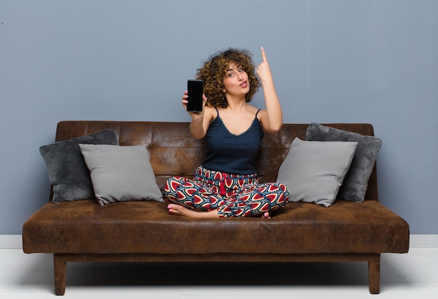 Giovane bella donna a casa, con un telefono cellulare, indossa un pigiama su un divano