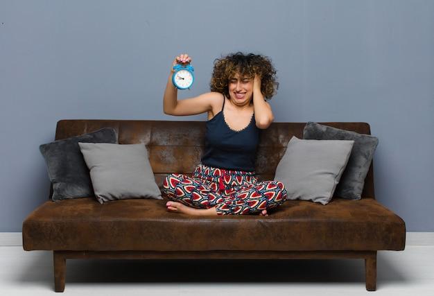 Giovane bella donna a casa seduta su un divano con un orologio