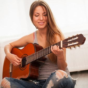 Giovane bella donna a suonare la chitarra