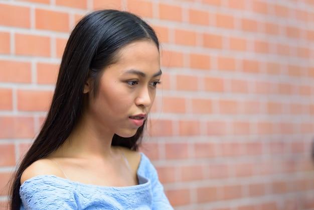 Giovane bella donna adolescente asiatica pensando mentre guardando verso il basso contro il muro di mattoni