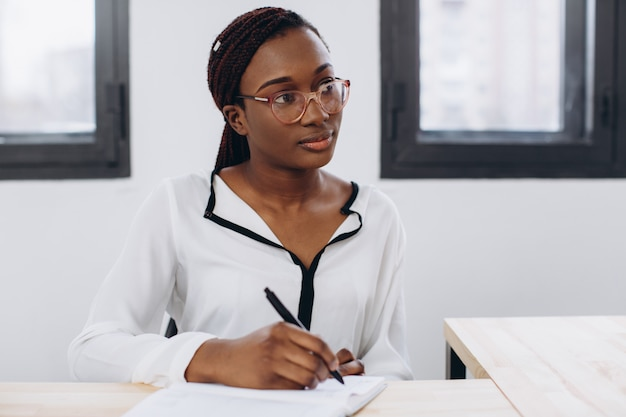 Giovane bella donna africana che ha un'intervista o una riunione d'affari con il datore di lavoro. datore di lavoro che esamina in un interno moderno dell'ufficio
