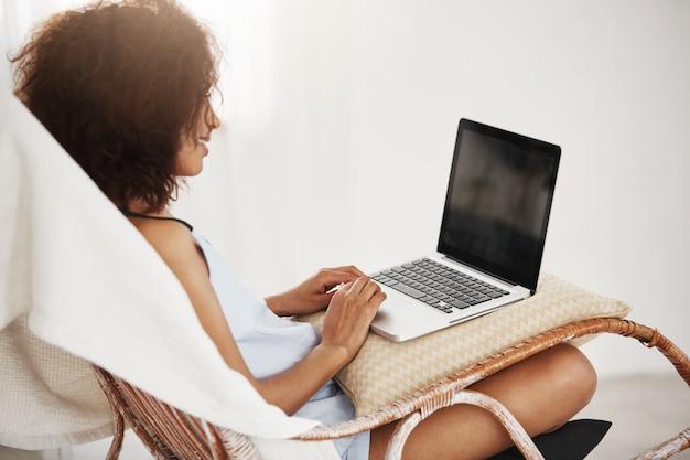 Giovane bella donna africana nella seduta sorridente di profilo con il computer portatile in sedia che lavora al suo diploma.