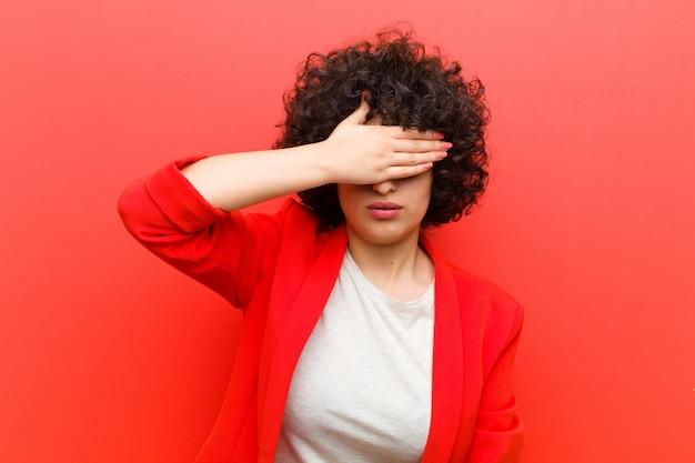 Giovane bella donna afro che copre gli occhi con una mano sentendosi spaventata o ansiosa, chiedendosi o aspettando ciecamente una sorpresa