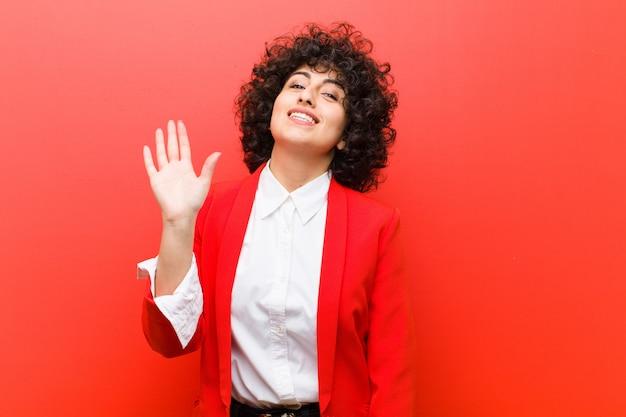 Giovane bella donna afro che sorride allegramente e allegramente, agitando la mano, dandovi il benvenuto e salutandovi, o salutandovi