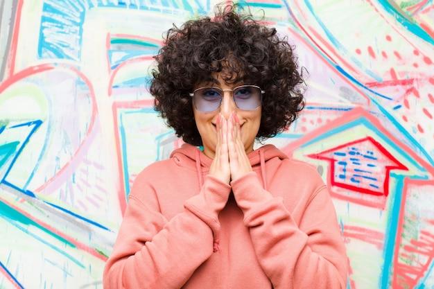 Giovane bella donna afro felice ed eccitata, sorpresa e stupita che copre la bocca con le mani, ridacchiando con un'espressione carina contro il muro di graffiti