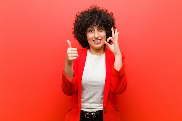 Giovane bella donna afro sentirsi felici, stupiti, soddisfatti e sorpresi, mostrando ok e pollice in alto gesti, sorridendo