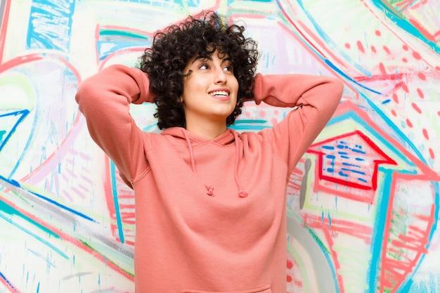 Giovane bella donna afro sorridente e sentirsi rilassata, soddisfatta e spensierata, ridere positivamente e rilassarsi contro il muro di graffiti