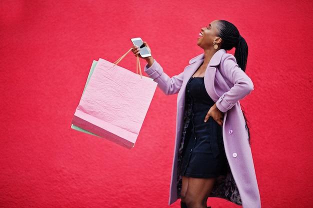 Giovane bella donna afroamericana alla moda contro il fondo rosso della parete, indossando il cappotto dell'attrezzatura di modo con i sacchetti della spesa e telefono cellulare a portata di mano.