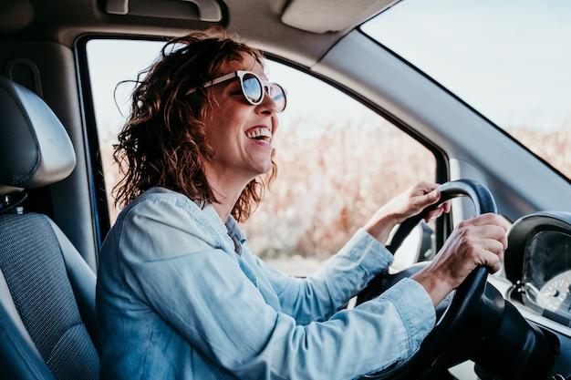 Giovane bella donna alla guida di un'auto. concetto di viaggio