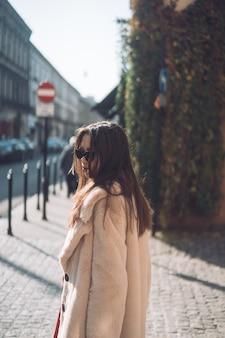 Giovane bella donna alla moda che cammina in cappotto rosa