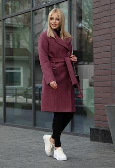 Giovane bella donna alla moda che cammina in strada, indossa cappotto, vestito di moda, tendenza autunno.