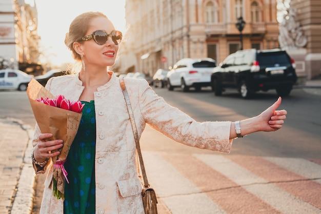 Giovane bella donna alla moda che cammina sulla strada della città sul tramonto, prendendo un taxi