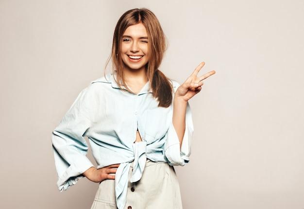 Giovane bella donna alla ricerca. ragazza alla moda in abiti casual estivi. modello divertente positivo. strizza l'occhio e mostra il segno di pace