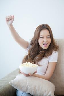 Giovane bella donna allegra che tiene ciotola di popcorn