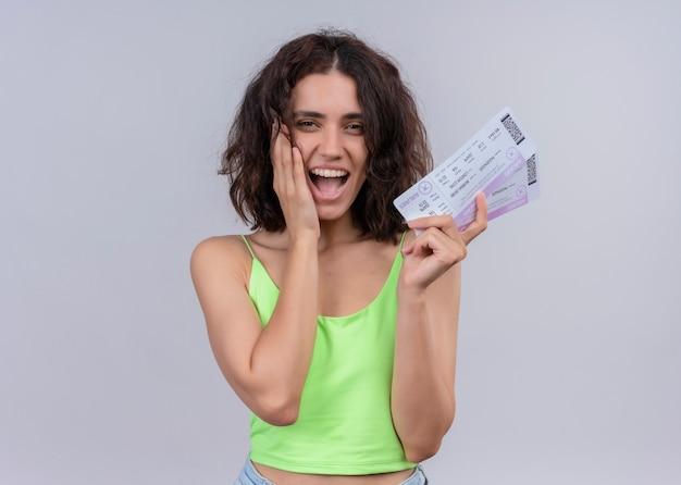 Giovane bella donna allegra che tiene i biglietti aerei e che mette la mano sulla guancia sulla parete bianca isolata