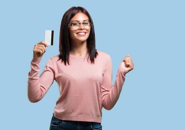 Giovane bella donna allegra e sorridente, molto eccitato tenendo la nuova carta di credito