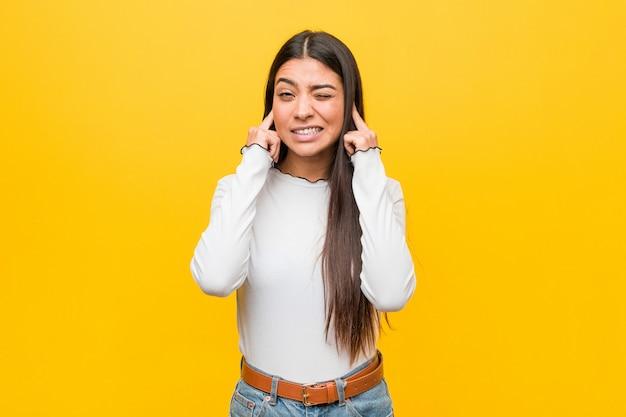 Giovane bella donna araba contro uno sfondo giallo che copre le orecchie con le mani.